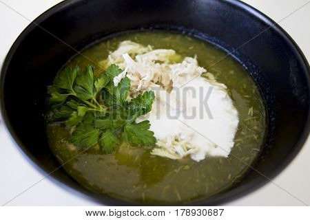 green soup from spinache and brocolli with chicken and crem in the black plate and snacks