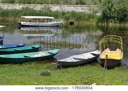 Few rowboats and turist boats moored between the rich coastal vegetation in the lake