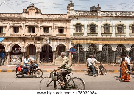 MYSORE, INDIA - FEB 20, 2017: Bicycle and rushing motorcycles on historical street of indian city on February 20, 2017. Mysore of Karnataka has a population of 900000