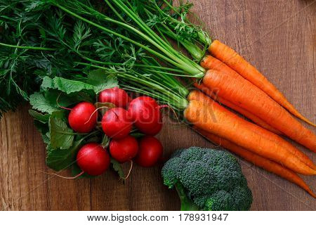 Carrot, red radish and brocoli. Fresh natural vegetables. Organic bio food on wooden table.