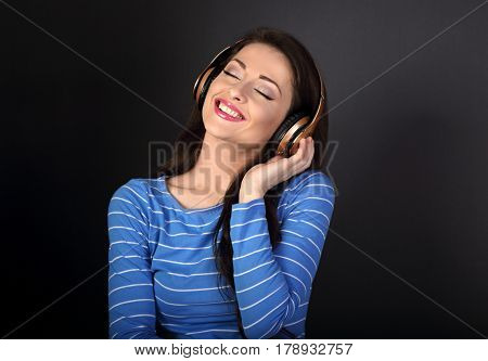 Beautiful toothy smiling young woman in blue clothing listening the music in wireless headphone with closed eyes on dark grey background