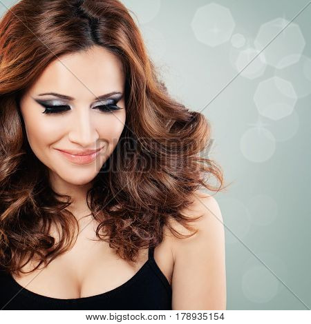 Beautiful Woman with Party Makeup and Red Curly Hair on Background with Copyspace. Redhead Fashion Model Face Closeup