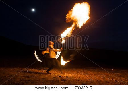 fire show, dancing with flame, male master fakir blowing fire, performance outdoors, flame control man dances with fire, draws a fiery figure in the dark, highly in mountains with a moon in a dark blue sky