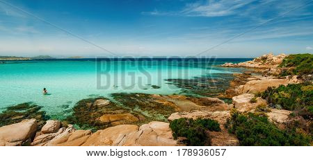 Wild beautiful rocky beach with turquoise transparent water and large stones in Vourvourou Sithonia Greece
