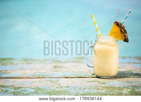 Exotic pineapple cocktail near pool. Pina colada