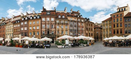 Warsaw Poland - May 28 2015: Panoramic view of old architecture of Warsaw. Traditional cafe with tourists against typical old houses on Old town Market square in Warsaw in a summer Poland