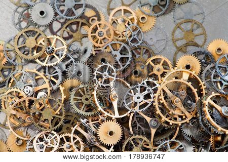 Pile of aged gears cogwheels macro view. Steampunk mechanical equipment and mechanism background. Shabby grunge scratch metal texture. Shallow depth of field.