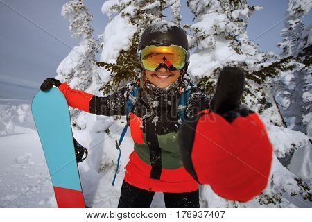 Girl snowboarder shows thumb. Positive image of winter recreation.