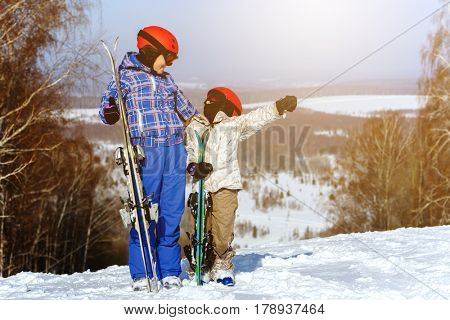 Mom and daughter, in ski equipment play with snow in the ski resort