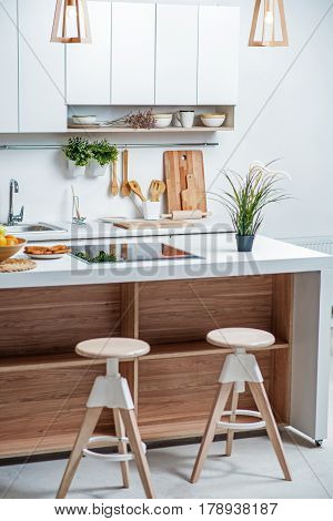 Luxury contemporary design in domestic kitchen. Wooden chairs near white counter with stove and fresh breakfast