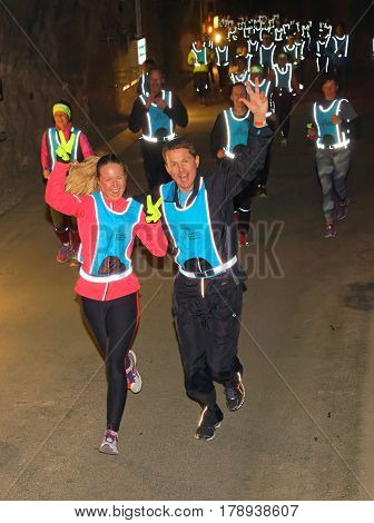 STOCKHOLM SWEDEN - MAR 25 2017: Happy couple in reflex vest running in a dark tunnel in the Stockholm Tunnel Run Citybanan 2017. March 25 2017 in Stockholm Sweden