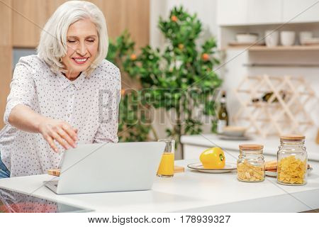 Portrait of joyful senior mother is using computer for communication. She is standing near table in cook room and adjusting technology. Woman is smiling