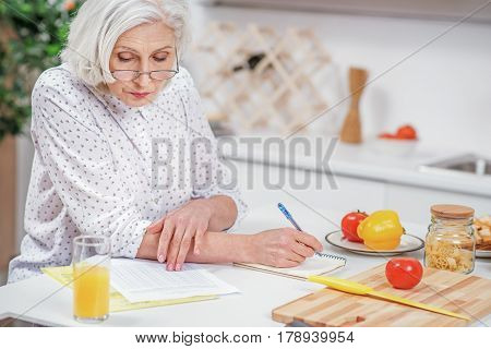Concentrated senior woman is working with utility bills at home. She is sitting at table and making notes with seriousness