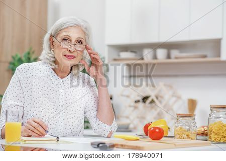 Portrait of cheerful senior housewife is calculating domestic expenses in kitchen. She is sitting at table and looking at camera with satisfaction