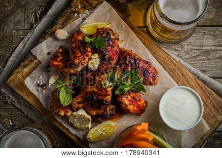 Chicken wings on wood board with beer and vegetable sticks