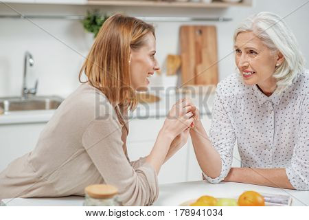 Thank you for everything. Grateful young daughter is touching arm of her mom with love. They are relaxing at home and smiling