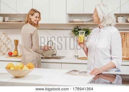 Just relax and I will do all housework. Caring young woman is washing the dishes and smiling. Her mother is drinking juice and looking at her with proud