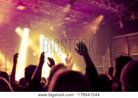 Blurred Background, Bokeh, Silhouette Of Cheering Audience, Hands Up And Musicians On The Stage With