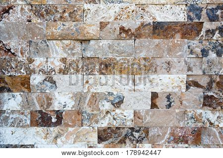 Pattern of colored marble stone decorative brick wall texture and background. Closeup of building facade
