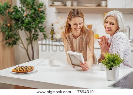 This is great photo. Happy senior woman is looking at photo frame with pleasure. Her daughter is sitting near her and laughing