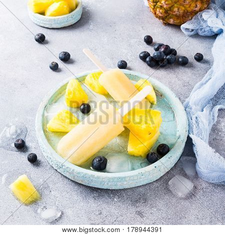 Pineapple popsicles with fresh blueberries on gray background. Healthy food concept. High angle view.