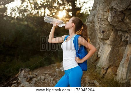 Pretty hiker girl drinking water. Thirsty woman tourist with backpack drinks water outdoors. Shapely female drinks clear water out of bottle backlit with sun. Refreshing healthy lifestyle concept
