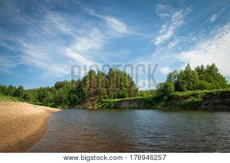 Beautiful river flowing in the countryside on a Sunny summer day. High Bank with beautiful old pine trees long sandy beach. A fisherman near the river. Blue sky with white clouds