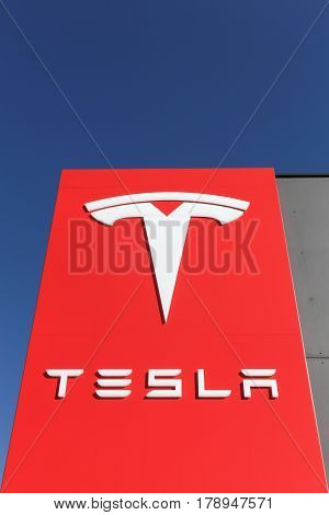 Tilst, Denmark - March 26, 2017: Tesla logo on a wall. Tesla is an American automotive and energy storage company that designs, manufactures, and sells luxury electric cars