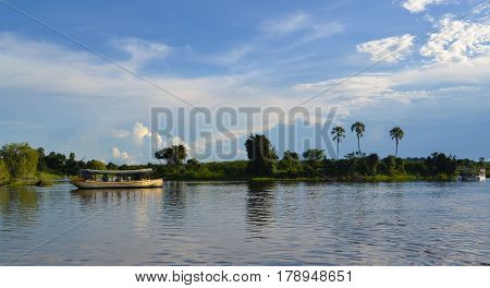 Zambezi river. Boat cruise. Boat in river. Boat on water. Sunset river. Boat at sunset. Boat travelling on river. Boat with reflection on water.