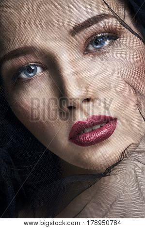 Widow in veils portrait of young brunette woman against a dark background. Mysterious bright image of a woman with professional makeup. Veil on the woman's face