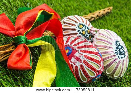 decorated Easter whip and painted decorated Easter eggs in spring grass
