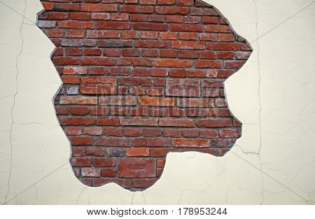 A cracked old wall reveal a brick wall inside