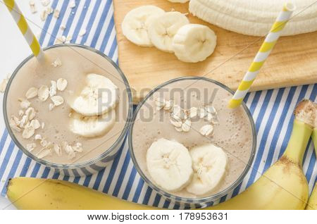Useful smoothies with a banana and oatmeal on a white background, in glass bowls on a striped tablecloth. View from above