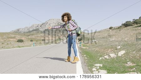 Young female tourist hitch hiking