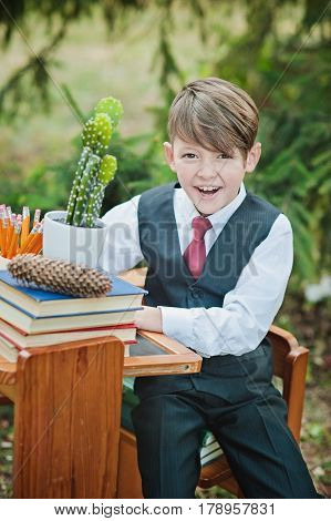 Portrait Of A Smily First-grader Boy Sitting At A Desk