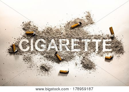 Cigarette word text written in ash filth or dirt with orange cigarette butts around as smoking passion health danger nicotine lust sickness and illness concept background