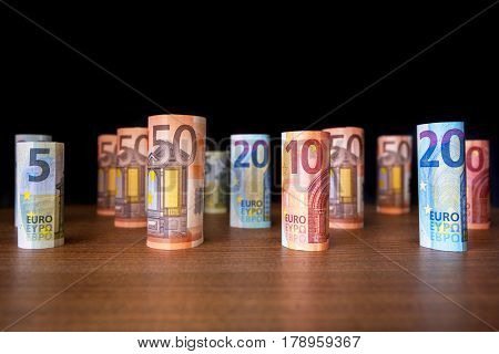 Rolled up euro banknotes on the desk