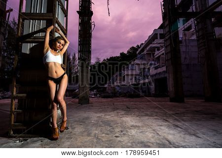 Asian Girl Posing In Abandoned Building. Looking In Camera