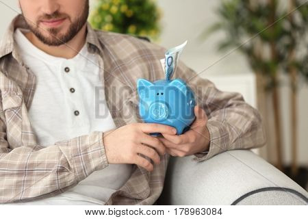 Happy young man sitting on sofa with piggy bank