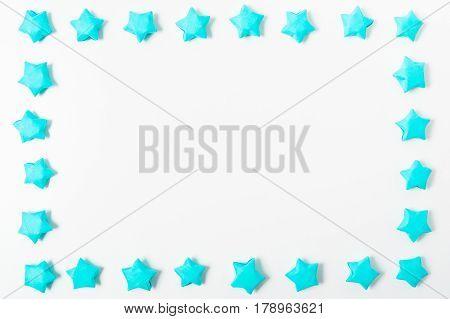 Blue handmade paper stars frame on white background