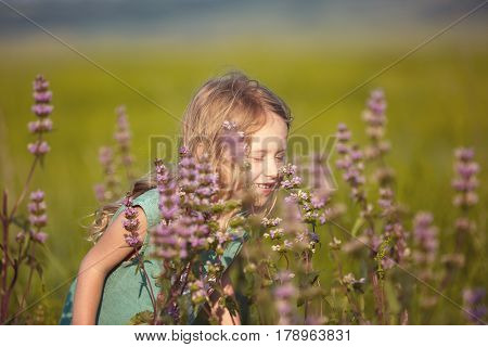 happy smiling girl in the field at sunny summer morning. girl in green dress Collects a bouquet of wildflowers. The family travels, the children happily ran around the field
