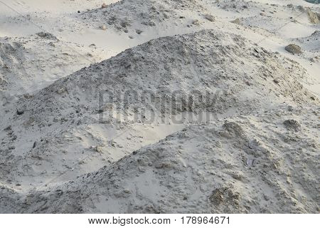 Smooth surface of sand dunes, uneven due to the existing stones, can be used as a nature background