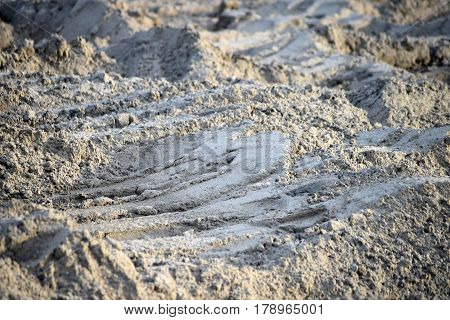 Deep prints on the uneven sandy surface, wallpaper with nature as a theme