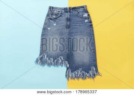 Blue denim skirt isolated on blue and yellow background