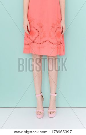 Woman long legs in summer dress, high heels. Perfect female sexy legs, stylish orange skirt on blue background