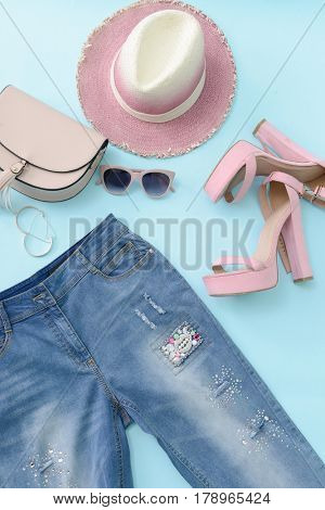 Jeans with sunglasses ,hat, handbag on blue background.