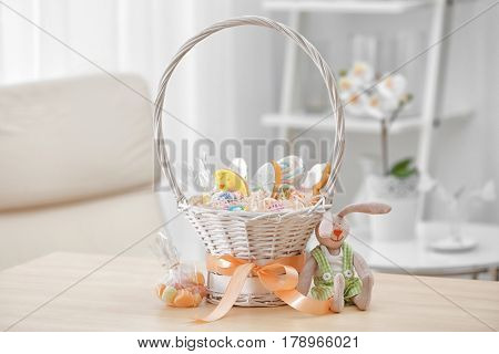 Delicious gifts in Easter basket on blurred background