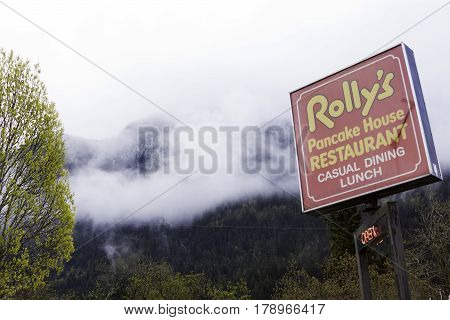 Hope, British Columbia - April 24, 2015 -- Wide view looking at the bright red sign at Rolly's Restaurant in Hope, British Columbia on a bright overcast day in April.