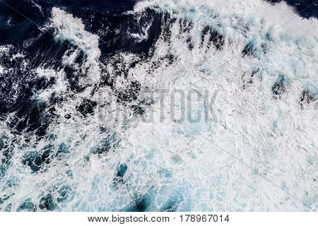 Background blue waves of the sea with sea foam