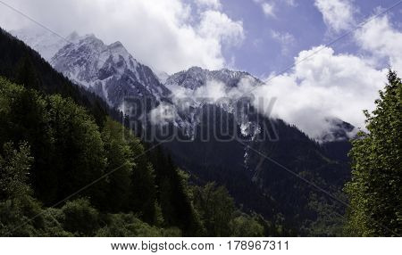 Wide view of the snow capped Rockies along the Trans Canada Highway with green trees and foliage just outside of Hope, British Columbia on a bright sunny day with blue skies and clouds in April.